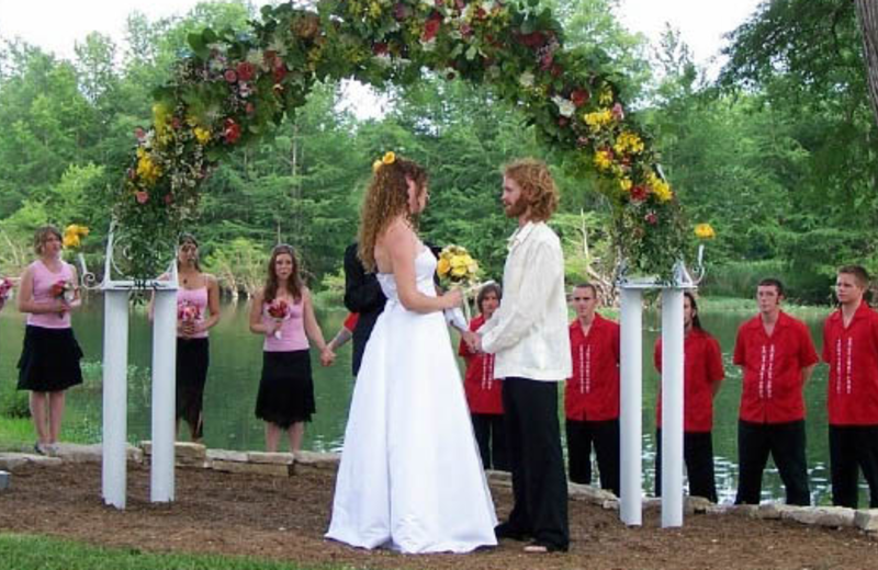 a wedding with an arch in the background